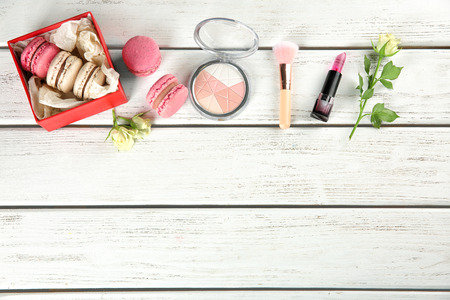 Flat lay composition with tasty macarons, roses and cosmetic products on wooden background