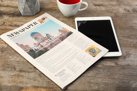 Newspaper with cup of tea and tablet computer on table