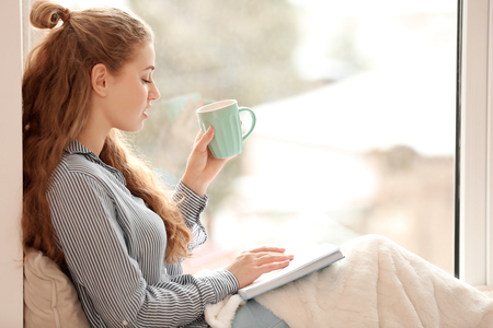 Young woman drinking tea while reading book near window indoors