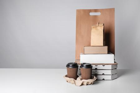 Diferentes paquetes y vasos de cartón en la mesa con fondo de color. Servicio de comida a domicilio