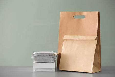 Diversi pacchetti sul tavolo su sfondo colorato. Servizio di consegna cibo