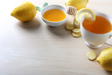 Cup of delicious tea with ginger, lemon and honey on table
