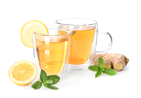 Cups of delicious tea with ginger and lemon on white background