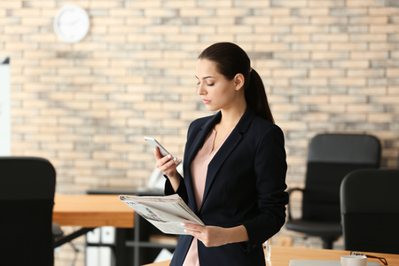 Young businesswoman with mobile phone and newspaper in office Archivio Fotografico