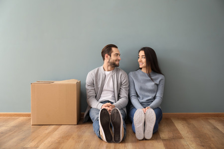 Young couple sitting on floor near box indoors. Moving into new house Stock Photo