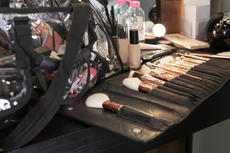 Collection of professional makeup brushes on table in beauty salon