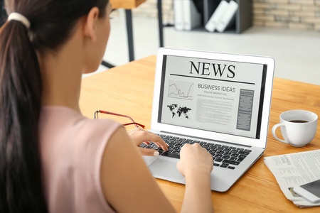 Young businesswoman reading news on laptop screen in office Imagens