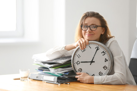 Mature tired woman with clock at table in office. Time management concept