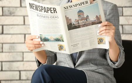 Young businesswoman reading newspaper against brick background