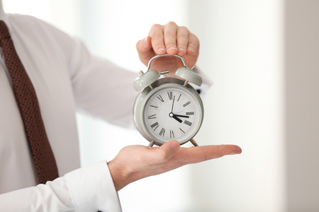 Businessman with alarm clock in office. Time management concept