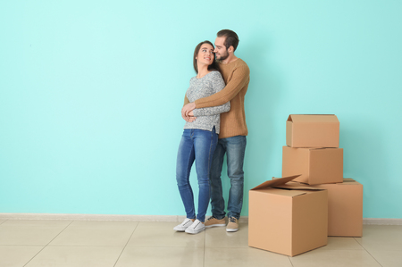 Young couple hugging near boxes indoors. Moving into new house