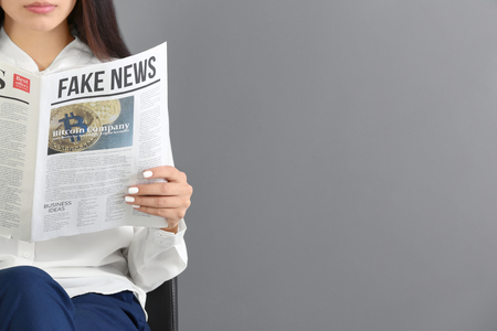 Young woman reading newspaper against grey background Stockfoto