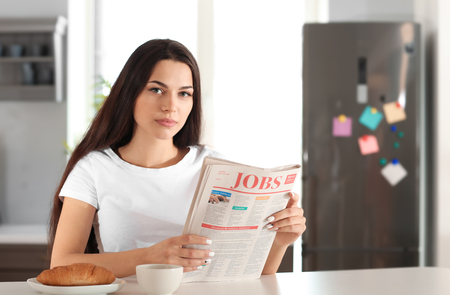 Young woman reading newspaper in kitchen