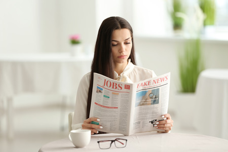 Young woman reading newspaper in cafe