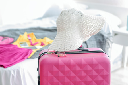 Beach hat and sunglasses on travel suitcase indoors
