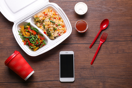 Flat lay composition with smartphone and takeout meal on wooden background. Food delivery Archivio Fotografico