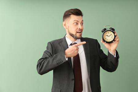 Businessman with alarm clock on color background. Time management concept Banque d'images