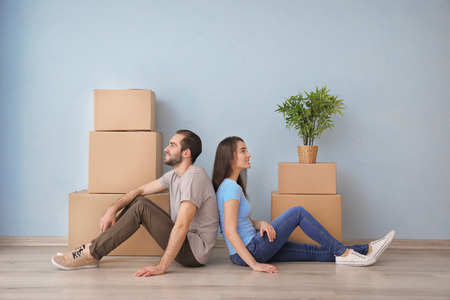 Young couple resting near boxes indoors. Moving into new house