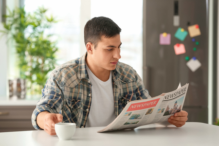 Man reading morning newspaper during breakfast at home Archivio Fotografico