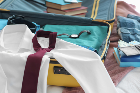 Open travel suitcase with clothes on bed