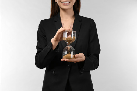 Woman holding hourglass on light background. Time management concept