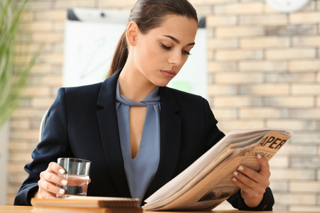 Young woman reading newspaper while drinking water in office