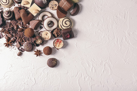 Yummy chocolate candies on white textured background