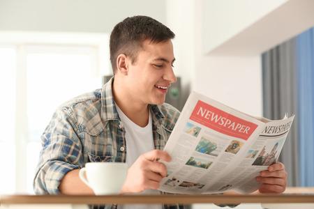 Uomo che legge il giornale del mattino durante la colazione a casa