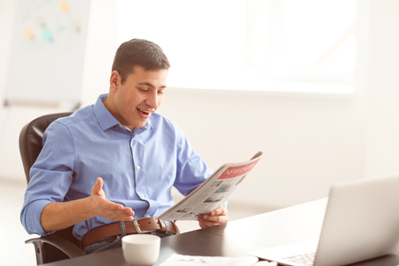 Handsome businessman reading newspaper in office