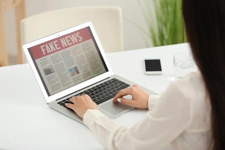 Giovane donna che legge notizie sullo schermo del laptop al chiuso