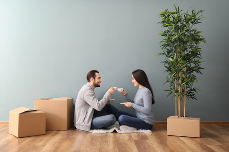 Young couple drinking coffee near boxes indoors. Moving into new house