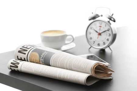 Morning newspapers, cup of hot coffee and alarm clock on grey table