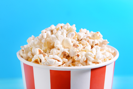 Paper bucket of tasty popcorn on color background, closeup