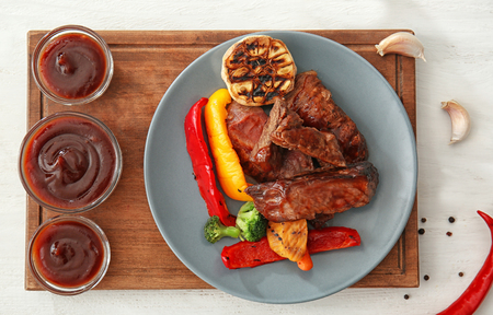 Bowls of barbecue sauce with grilled meat on wooden board