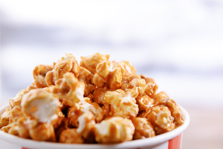 Paper bucket of tasty caramel popcorn, closeup