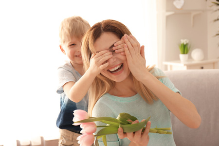 Cute little son surprising his mother with flowers at home