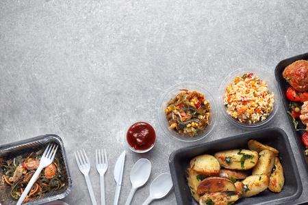 Diferentes recipientes con deliciosa comida sobre fondo gris
