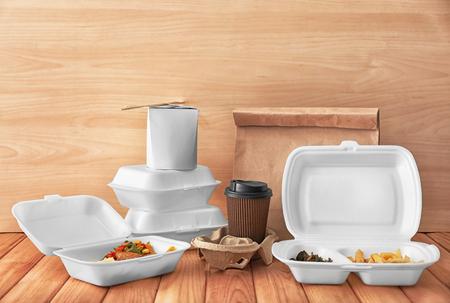 Recipientes con comida deliciosa y una taza de café en la mesa de madera