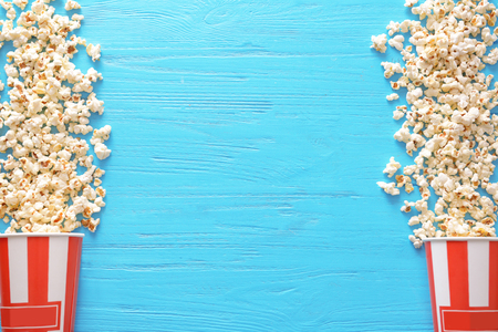 Paper buckets with tasty scattered popcorn on color wooden background Stock Photo