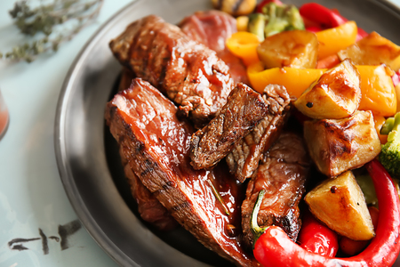 Grilled meat with vegetables on table, closeup Imagens