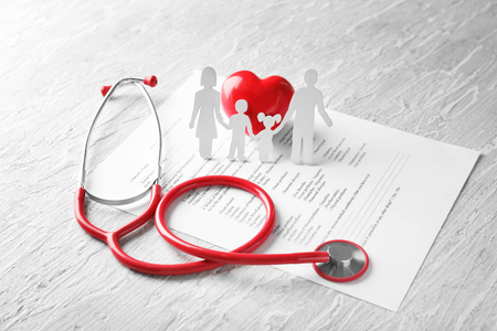 Composition with family figure and stethoscope on wooden background. Health care concept
