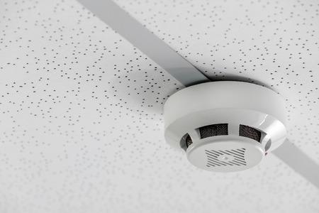 Modern smoke detector on ceiling indoors