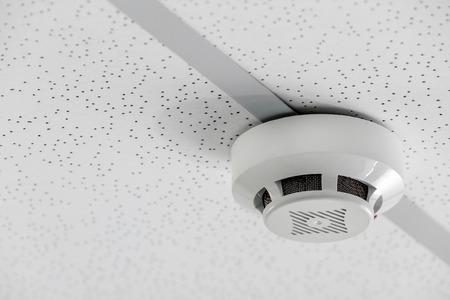 Modern smoke detector on ceiling indoors Foto de archivo - 113249161