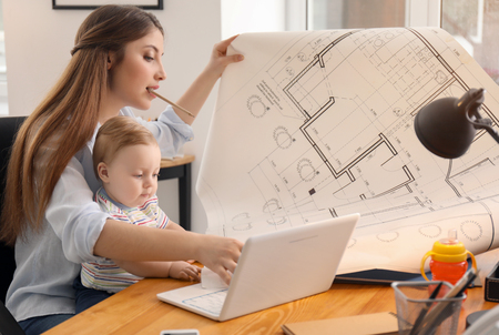 Young woman with baby working in office