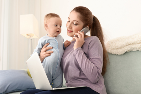 Young mother holding baby while working at home