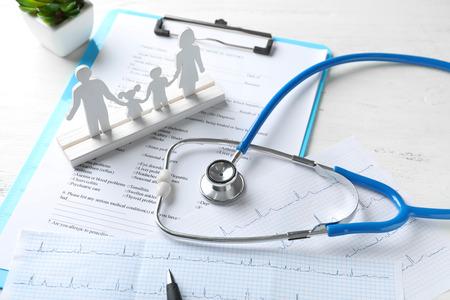 Composición con figura familiar y estetoscopio sobre mesa de madera. Concepto de cuidado de la salud