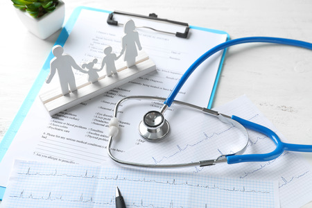Composition with family figure and stethoscope on wooden table. Health care concept Stockfoto