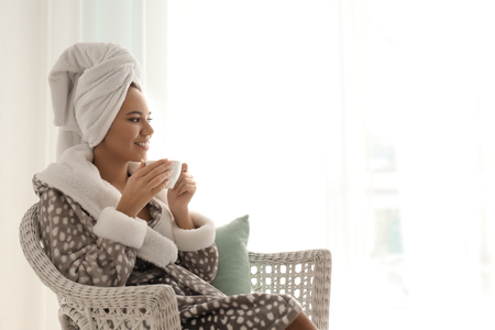 Morning of beautiful African-American woman drinking coffee at home