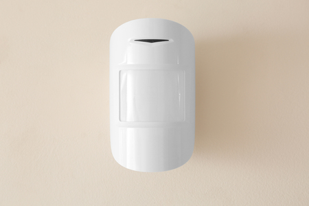 Modern motion sensor on wall indoors
