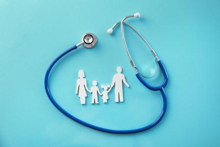 Familienfigur und Stethoskop auf farbigem Hintergrund. Gesundheitskonzept